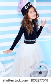 Beautiful lady curly hair small little girl child funny cute face smile sweets baby shower party candy bar game room birthday wear white skirt black t-shirt beret hat socks clothes blue strip wall.