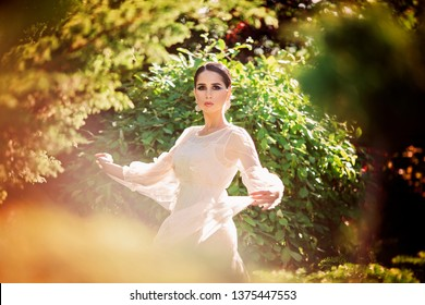 Beautiful lady dancing in sunlight garden. Dreamy portrait of young woman in vintage dress. Beauty fairy-tail wedding concept.