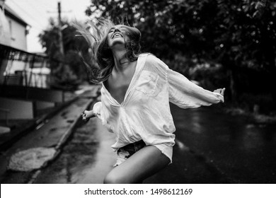 Beautiful lady enjoys fresh rai, she walking outdoor in wet clothes and laughing. White big shirt on her sexy body, short jeans. Tanned soft skin, long hair, white smile. Trees and road behind