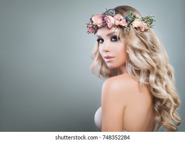Beautiful Lady Fashion Model with Roses Flowers and Green Leaves in her Hair. Cute Woman with Blonde Curly Hairstyle and Healthy Skin, Skincare and Haircare Concept