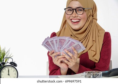 Beautiful lady happily  holding and showing money isolated on a white background