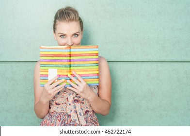 Beautiful lady holding diary and covering her mouth on green wall background with copy text area