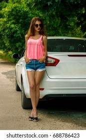 beautiful lady in hotpants and a pink t-shirt standing near the car