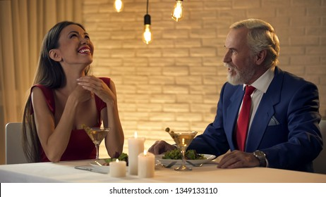 Beautiful lady laughing and flirting with old rich man in restaurant, escort