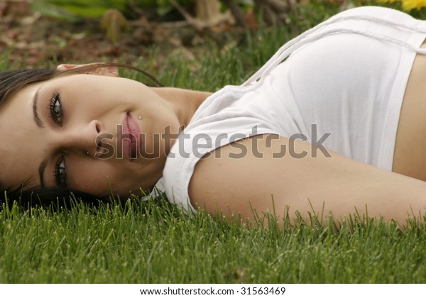 Beautiful lady laying in the grass with piercing