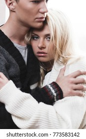 Beautiful lady leans to man's shoulder while he hugs her