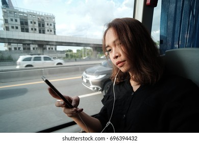 A beautiful lady is listening to a song when she on the way to airport. A cute girl is playing her smartphone and enjoy it.