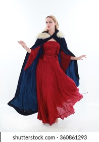 beautiful lady with long blonde hair wearing a red medieval fantasy gown and a blue fur cloak. standing, isolated on white background.