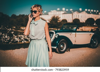 Beautiful lady with mobile phone near classic convertible.