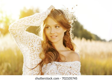 Beautiful lady model posing in an open field at golden hour - close up shot