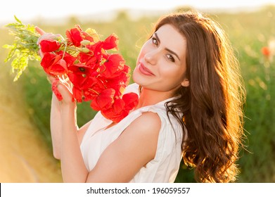 Beautiful lady over Sky and Sunset in the field holding a poppies bouquet, smiling, wind in her hair. Freedom concept. Series. Free Happy Woman Enjoying Nature