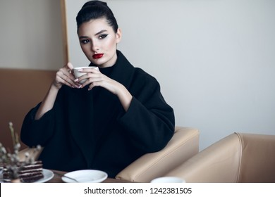 Beautiful lady with perfect make up sitting in the nice cafe drinking coffee and eating cake. Coffee time concept. Text space