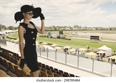 beautiful lady in a proper outfit for horse racing day on the Melbourne Cup event on hippodrome, fashion on the field