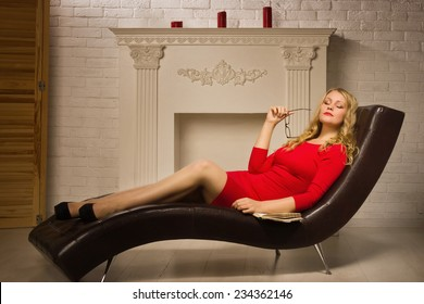 Beautiful lady in a red dress sitting on the couch  in the vintage interior