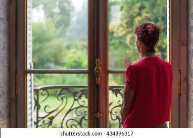 A Beautiful lady in a red top is daydreaming while looking out a window to a lush country garden outside.