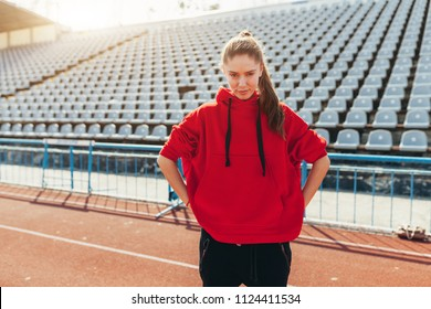 Beautiful lady runner in warm clothes on the stadium looking aside. Wearing red hood. Casual sport wear concept.