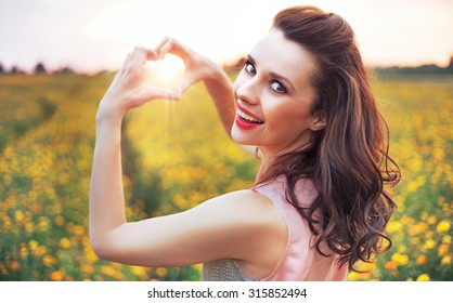 Beautiful lady showing heart symbol