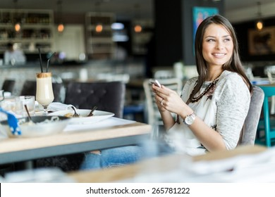 Beautiful lady sitting in a bar and smiling while holding cell phone