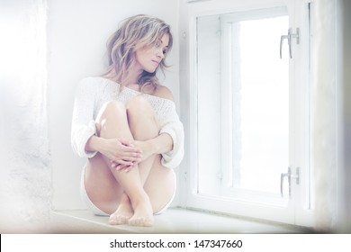 Beautiful lady sitting by the window
