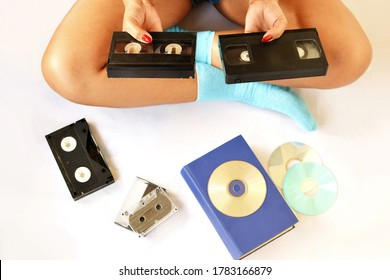 A beautiful lady sitting on bed and looking at her old video tapes