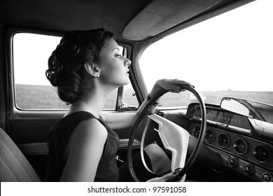 Beautiful lady sitting in a retro car