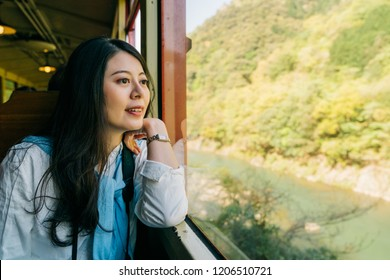 beautiful lady sitting in the sightseeing train and looking at scenery outside the window. Asian woman relaxing in train seat. Chinese young girl enjoying view.