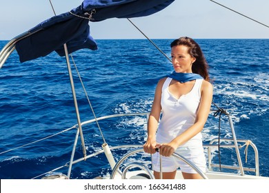 Beautiful lady skipper navigating a sailboat.