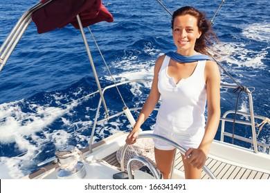 Beautiful lady skipper navigating a sailboat.