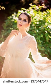 Beautiful lady in sunlight garden. Dreamy portrait of young woman in vintage dress. Beauty fairy-tail wedding concept.