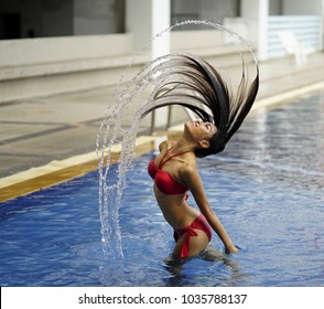 Beautiful Lady in swimming pool. woman flicking her hair and water trail splash at the water fall day time. Hair Splash. hair Whips In Water. photo of a sexy bikini model flicking her hair and water