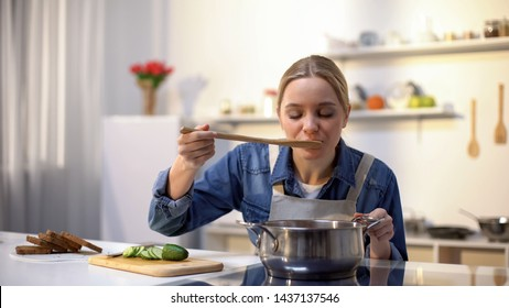 Beautiful lady tasting soup while cooking, preparing food for dinner, dieting