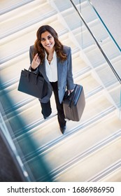 Beautiful lady with travel suitcase standing on white staircase and smiling stock photo