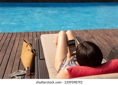 Beautiful lady using cell phone lying on chair with man swimming in the pool