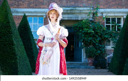 Beautiful lady wearing vintage regency dress and bonnet, carrying a parasol and standing outside of stately home
