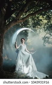 Beautiful lady in wedding dress standing near mirror moon. Fairytale wedding