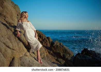 Beautiful lady in white dress on rocky shore