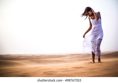 Beautiful lady in white dress standing in the harsh desert