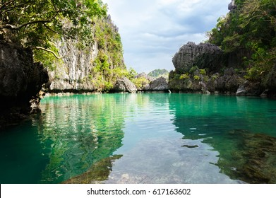 beautiful lagoon with crystal clear turquoise water surrounded by high cliffs on the island of Palawan Philippines