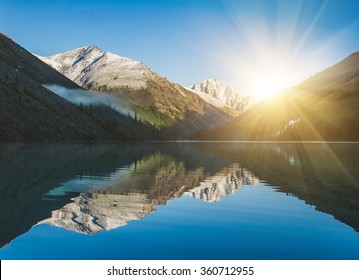 Beautiful lake in Altai. Sunrise and mountains reflected in the water