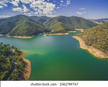 Beautiful lake among forested hills on bright sunny day