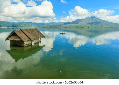 Beautiful Lake Batur landscape overlooking serene and beautiful Mount Batur during blue sky cloudy day with abandoned sub-merge house at foreground.