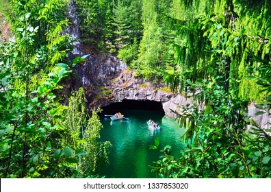 Beautiful lake with brigh emerald water, deep cave under bare rock, lush foliage and two rowing boats in old abandoned marble quarry, Ruskeala park, Republic of Karelia (Kareliya), Northwest Russia