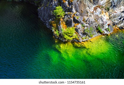 Beautiful lake with brigh water in green tones and bare rock with firs and moss in old abandoned marble quarry, Ruskeala, Republic of Karelia (Kareliya), Northwest Russia
