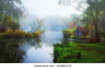 Beautiful lake covered in thick fog with small huts on the shore