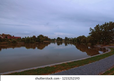 Beautiful lake during cloudy sunrise in Telc. Trees reflected in the water. Summer morning view. The historic center of Telc is a UNESCO World Heritage Site. Telc, Czech Republic.