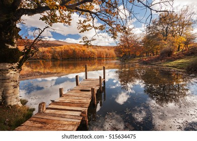 Beautiful lake during fall, with colorful trees reflected on the water.