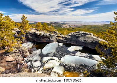 Beautiful Lake with ice in the rocky mountains with pine woods of Karkaraly national park in Central Kazakhstan