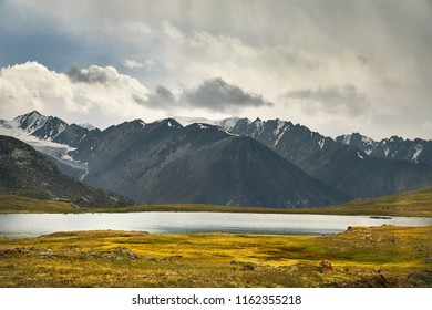Beautiful Lake and Mountain Range in the valley against cloudy sky in Kyrgyzstan
