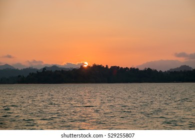Beautiful lake with mountains and sun set at ratchaprapa dam, khao sok national park in surat thani southern of thailand