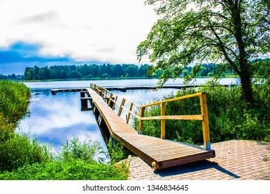 Beautiful lake park on a bright sunny summer day near Trakai Castle in Lithuania, Europe. Lake Galvė is a lake in Trakai Lithuania. Lake and Forest Panorama, blue sky, yellow boat dock.